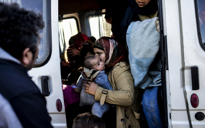 A woman holds an infant in a van after being detained by Turkish soldiers with other Syrians trying to reach the Greek island of Lesbos from Dikili, western Turkey, on March 5, 2016.