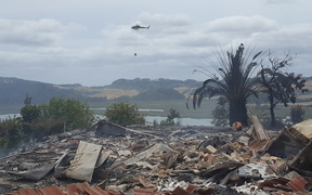 A monsoon helicopter flies over the remains of a house razed by a scrub fire near Whitianga. At least four houses and several other buildings have burnt to the ground.