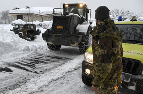 Civil defence and military vehicles clear snow from a central street of Aringo near Montereale in Italy after the earthquakes.