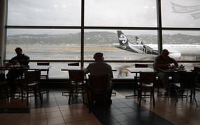 People wait at Wellington airport after foul weather forced the cancellation and delay of dozens of flights.