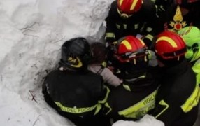 Rescue workers pull a survivor from under the snow.