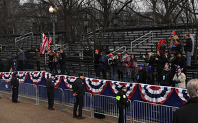 Supporters of US President Donald Trump and First Lady Melania Trump watch as they drive the inaugural parade route on Pennsylvania Avenue in Washington DC following swearing-in ceremonies on Capitol Hill.