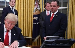 US President Donald Trump signs an executive order as Vice President Mike Pence and Chief of Staff Reince Priebus look on.