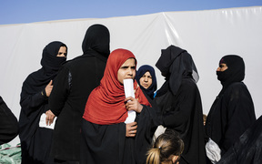 Displaced Iraqi women who fled the violence in the Islamic State group stronghold of Mosul, gather for food near the town of Bartella on 14 January, 2017, during a military operation by Iraqi security forces against IS fighters.