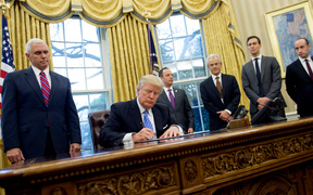 Donald Trump, seated, signed, three executive orders on Monday, including one banning any US-funded organisations from speaking about abortion.