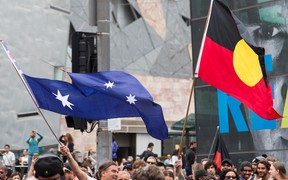 Protestors wave the Australian Flag with the Union Jack cut out and an Aboriginal Flag, during a protest, organized by Aboriginal rights activists on Australia Day in Melbourne,