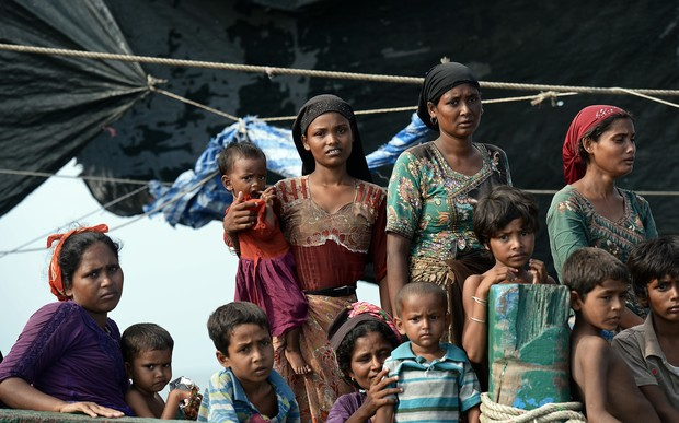 Rohingya migrants stand and sit on a boat drifting in Thai waters off the southern island of Koh Lipe in the Andaman sea on May 14, 2015