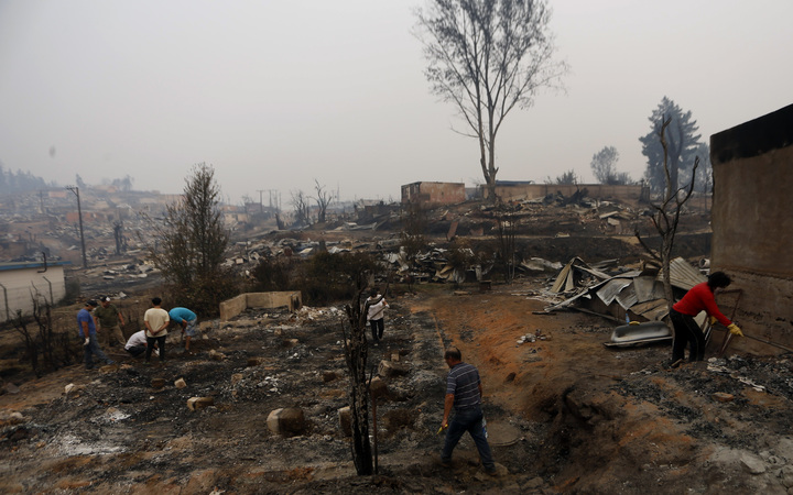 People work to clean up the debris after a forest fire devastated Santa Olga, 240 kilometres south of Santiago