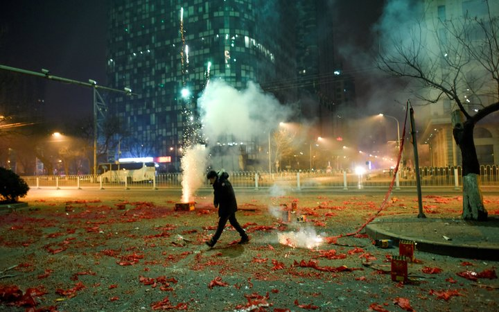 A man walks among firework papers in the streets of Beijing on 28 January, 2017, just after midnight marking the start of the Lunar New Year.