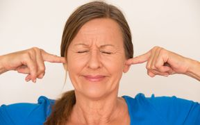 woman blocking her ears
