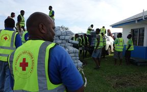 Vanuatu Red Cross workers load relief supplies brought in on a NZAF Hercules. Much needed tarpaulins, water containers and health and sanitation kits were being stored until further notice was given from the NDMO