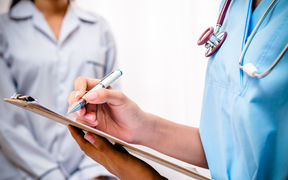 Doctor with clipboard takes patient's notes