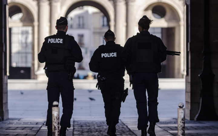 Police secure the area in front of the Louvre.