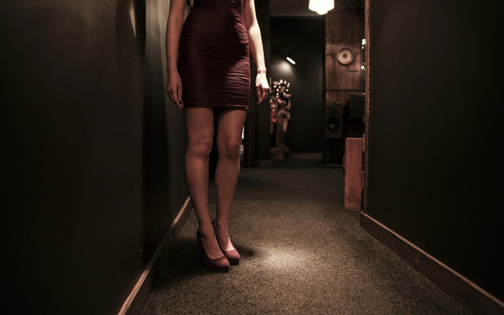 The Oldest Profession, a sex worker stands in the hall of the brothel she operates out of