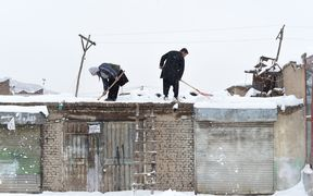 Afghan shopkeepers shovel snow from the roof of their shop during snowfall in Kabul on February 5, 2017.