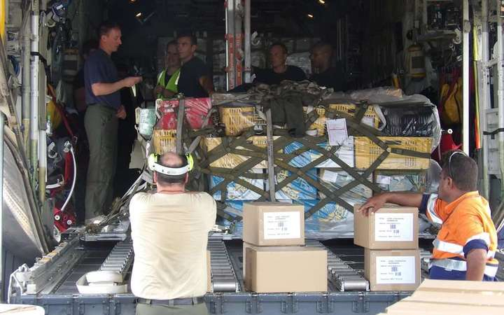 Crew from a Royal New Zealand Air Force C-130 Hercules aircraft begin to unload the estimated three tonnes of textbooks donated to Fiji's cyclone-damaged schools.