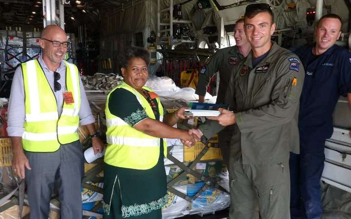 Flight Lieutenant Kendall Dooley, the captain of the Royal New Zealand Air Force hands over the textbooks to Merewalesi Vueti, the Director of Library Services in Fiji's Ministry of Education, as New Zealand High Commissioner to Fiji Mark Ramsden (left) looks on.