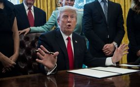 US President Donald Trump signs an executive order with small business leaders in the Oval Office at the White House in Washington DC on January 30