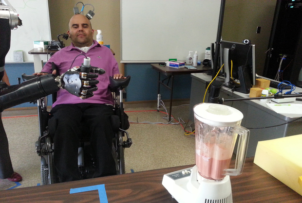 Erik Sorto uses a robotic arm controlled by his thoughts to operate a blender.