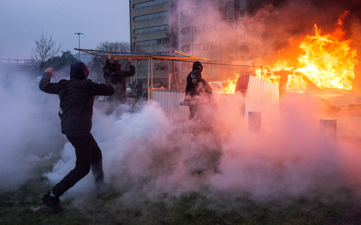 A car is ablaze in the Paris suburb of Bobigny during a protest against police brutality sparked by the arrest of a young man called Theo.