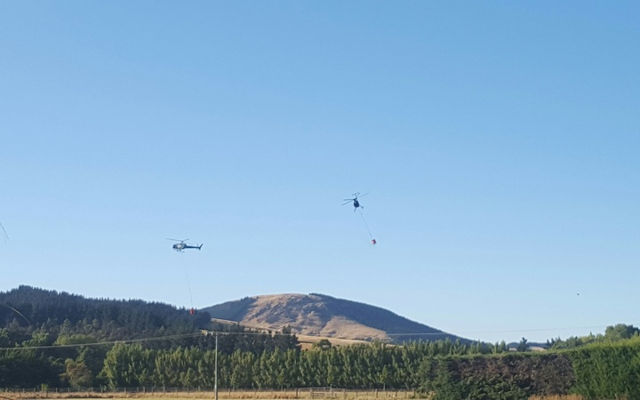 Helicopters with monsoon buckets tackle the Port Hills fire.