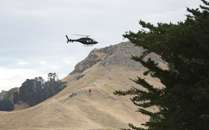 Helicopters with monsoon buckets work to douse the fires