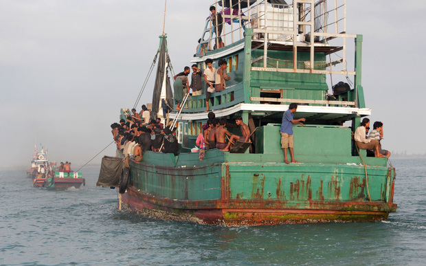 Fishermen help rescue a boat of Rohingya migrants off the coast of Indonesia's East Aceh on 20 May 2015.