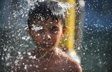 An Indian child cools off under a fountain at a water park in Hyderabad
