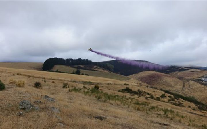 A plane dropping fire retardant over the Port Hills.