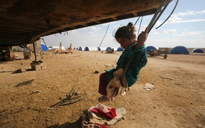 A displaced Iraqi girl plays on a swing at the Al-Agha camp where Iraqi families from the nearby villages of Tal Afar, southwest of Mosul, are taking shelter as Iraqi forces continue their military operation to recapture Mosul from Islamic State (IS) jihadists on February 16, 2017.