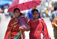 Two women and a child shelter under an umbrella in Hyderabad on Monday.