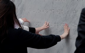 Members of the public, including the family and friends of victims, gathered to place their hands on the memorial.