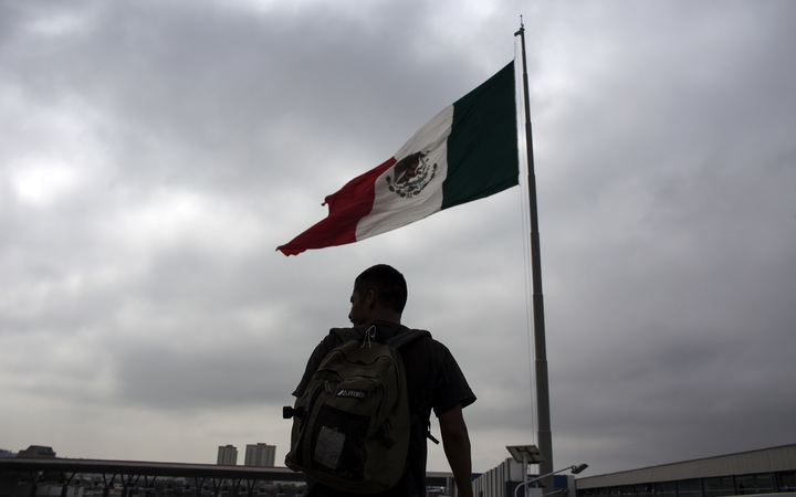 A Mexican deported from the US is seen next to a Mexican national flag at El Chaparral repatriation center in Tijuana, northwestern Mexico, in the border with the US.