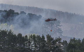 A helicopter flies in a load of water in a monsoon bucket during fire fighting efforts last Thursday in the Port Hills during the Christchurch fires. 16 February 2017