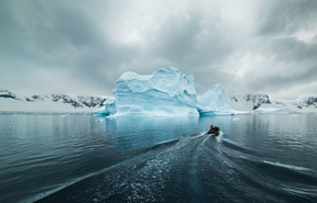 A small inflatable boat heads out to the iceberg Lincoln