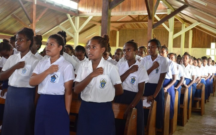 Students of Selwyn College sing the National Anthem.