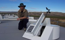 Dan Smale on top of the NIWA's Lauder atmospheric research laboratory building kneeling behind a solar tracker that feeds light into a Fourier transform spectrometer used to measure atmospheric trace gases.