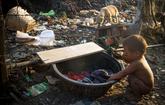 A child washes his face with laundry water among the trash and dogs in Tondo Landfill, Manila