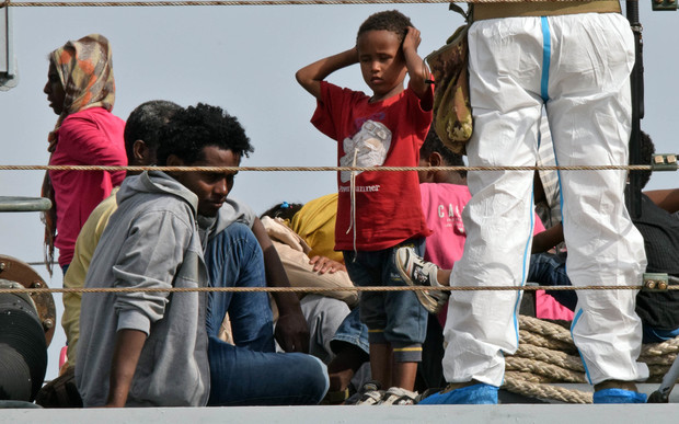 Migrants disembark from an Italian military ship at the port of Augusta, on the eastern coast of Sicily, on 21 May 2015.