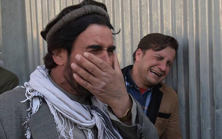 Two Afghan men weep for their relatives after gunmen dressed as doctors killed more than 30 people at a Kabul hospital.