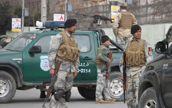 Afghan security forces block the roads after gunmen dressed as doctors attacked a Kabul hospital, killing 30 people.