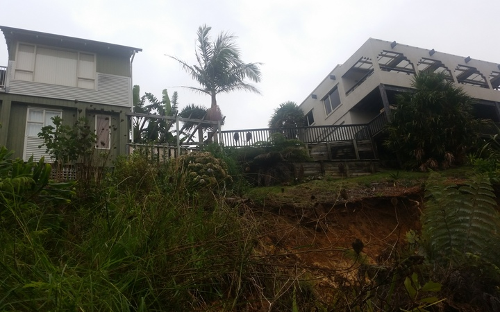 Michael Robertson's house (right) has been condemned until further notice because the soft ground underneath could mean his house goes down bank in another downpour.