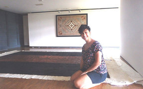 Ruha Fifita sitting in front of her enormous tapa, with another tapa by Christelle Montané on the wall.