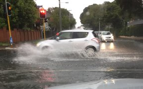 A car drives through surface flooding on Gillies Ave, Auckland.