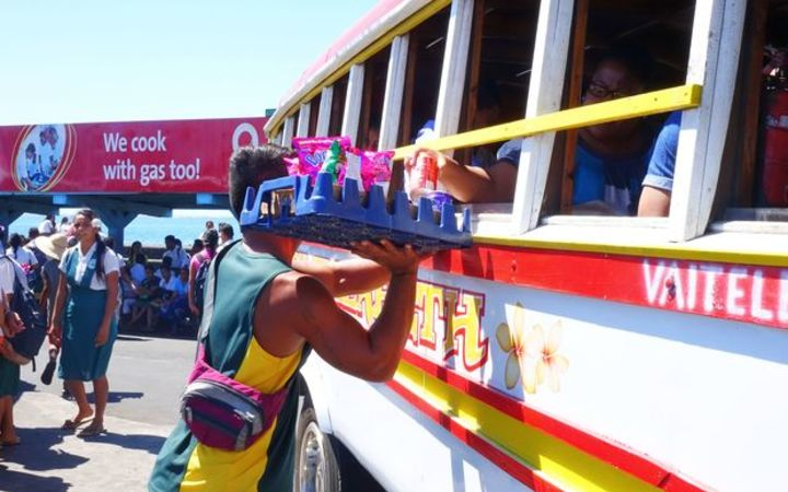 Street vendors at the Apia bus station can be seen winding in and out amongst the colorful Samoan buses selling food and drinks to passengers.