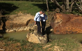 Primary Industries Minister Nathan Guy, left, and Hunua MP Andrew Bayly assess flood damage on a farm in rural Auckland.