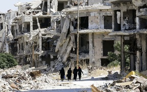 This file photo taken on September 19, 2016 shows Syrian women walking in between destroyed buildings in the government-held Jouret al-Shiah neighbourhood of the central Syrian city of Homs.