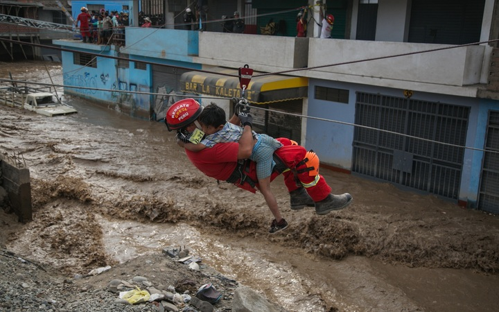 LIMA, PERU - MARCH 17 : Agents of the Peruvian National Police rescue people trapped in buildings due to the flooding of the Rimac and Huaycoloro rivers, in Lima, Peru on March 17, 2017.