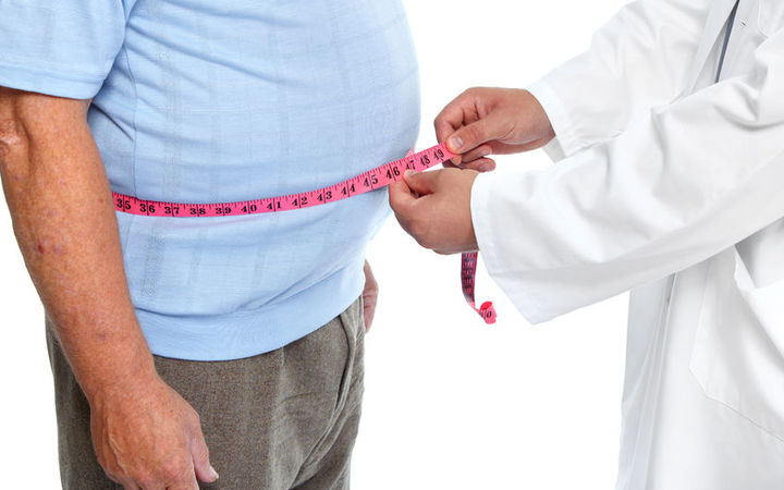 Doctor measuring waist of obese man (stock shot).