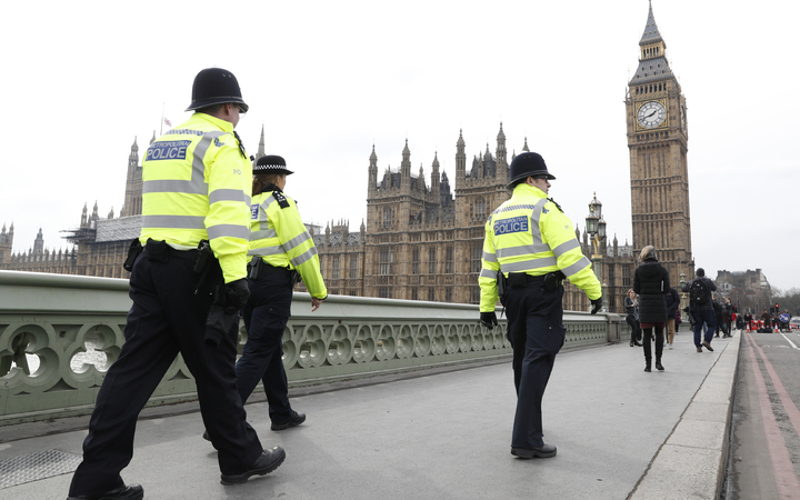 Police patrol across Westminster Bridge toward the Houses of Parliament.